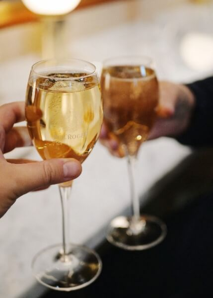 Två händer som håller i champagneglas som skålar