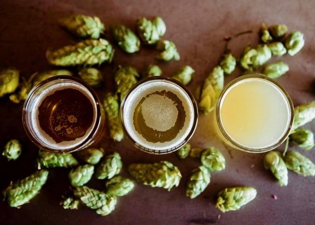 Tre ölglas på ett bord med öl i olika färger. Runt om glasen ligger humle.