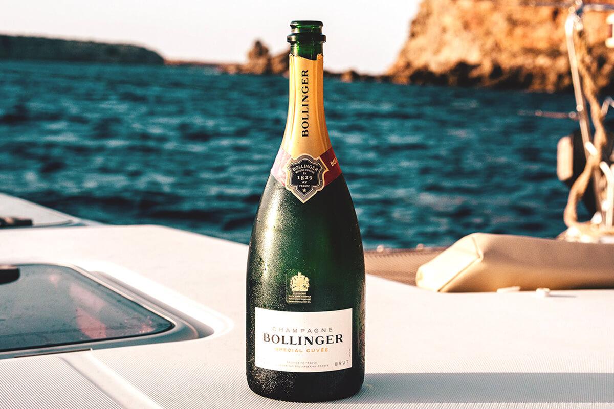 Champagne Bollinger-flaska står på en båt med vatten och klippor i bakgrunden