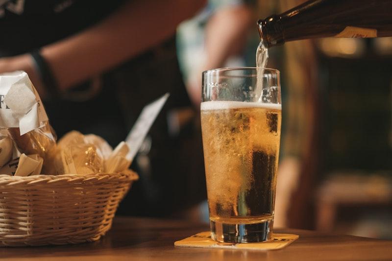 Öl hälls upp i ett ölglas vid sidan av en ostkorg
