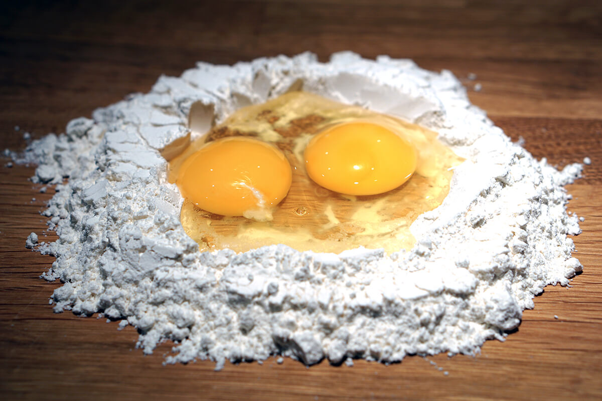 Gör egen pastadeg med mjöl format med en grop i mitten där ägg ligger