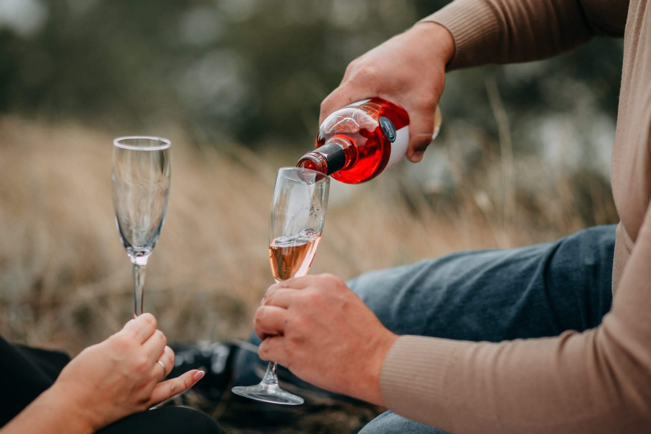 En man fyller två champagneglas med mousserande rosévin.