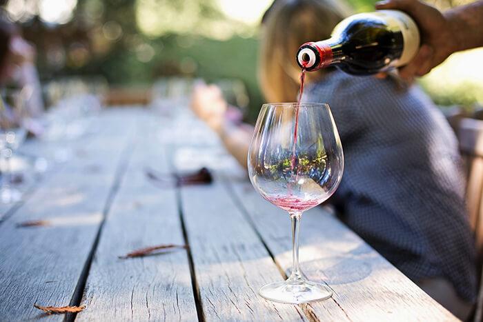 Rött vin hälls upp i vinglas i utomhusmiljö