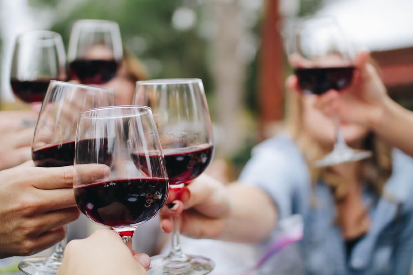 Vänner skålar med rött vin