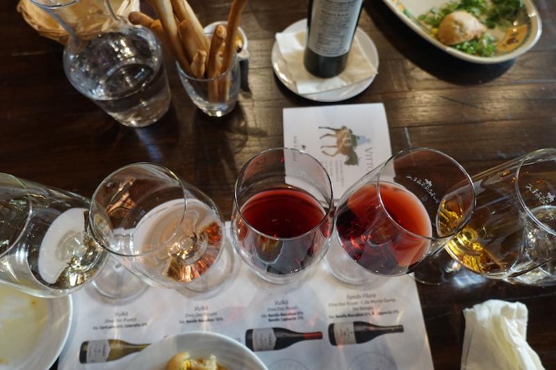 Olika viner på ett bord med tilltugg.