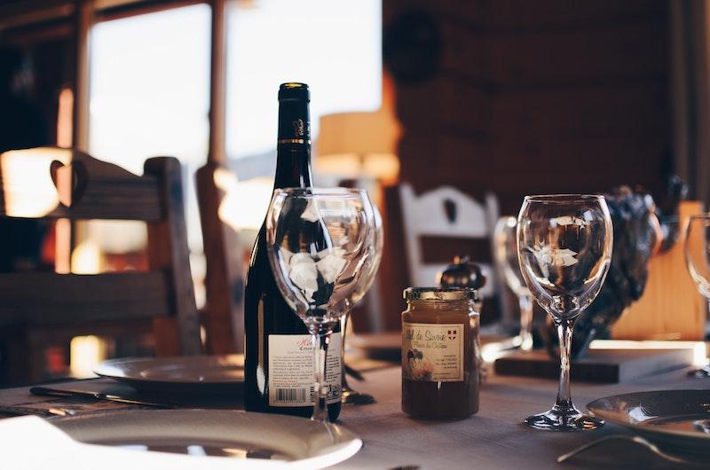 Vinflaska och glas vid dukat bord