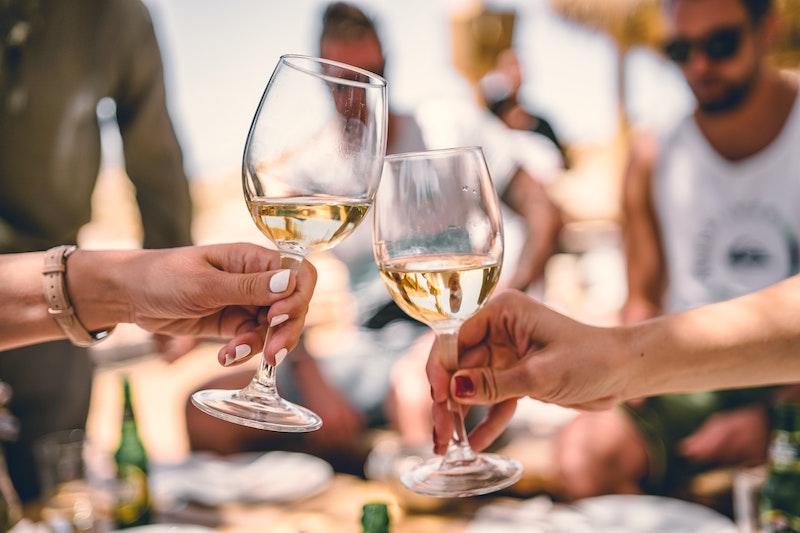 Två glas vitt vin som på en kräftskiva skålar.